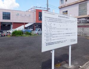 市が取得した用地には実施の看板が建てられているものの、完成年の部分は消えている