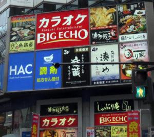 ビッグエコー新横浜店は、新横浜駅のペデストリアンデッキ(岸根側)を降りてすぐ、新横浜2丁目のマリノス通り(レンガ通り)沿いにある「YK-8ビル」の7~8階にある