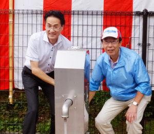 災害用に横浜市内で初めて公園に設置された「井戸」の水を流す横山港北区長(左)と新横浜町内会の金子会長(右)
