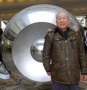 港北美術区民会の創設者で、現在も会長を務める佐々木義文(よしふみ)さん。日吉駅コンコース内の「虚球自像(こきゅうじぞう)」前で(2018年1月31日)