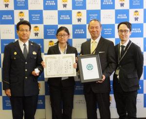 港北警察署で、ラグビーW杯や東京オリンピックのテロ対策協議会「オール港北」の記章デザインを行った上村絢音さんに対する感謝状の贈呈が行われた。左から牧署長、上村さん、三辻校長、指導教員の村田課長