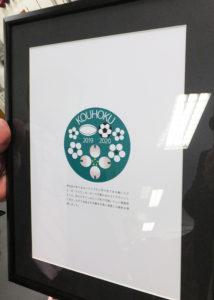 上村さんには受賞した記章デザインの額が贈呈された