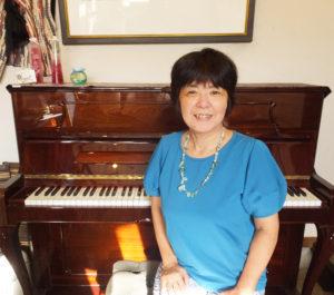 大倉山の街のピアノの先生としても地域の人々に愛されながら、NPO法人ハッピーマザーミュージックの運営も手掛ける理事長の鈴木美美子さん。鈴木さんのピアノでヨーロッパ・チェコ製の「ペトロフ」と(大倉山7丁目・夢うさぎにて)