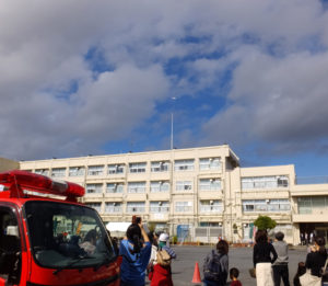 株式会社エムテックスは、昨年行われた新横浜駅での帰宅困難者対応訓練や、綱島東小学校で行われた地域防災訓練での、港北区内小学校での初ドローン実演に協力していた(2018年10月27日、同小学校での実演の様子)