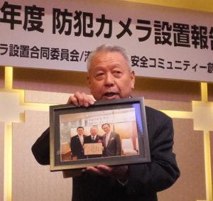 港北区防犯カメラ設置合同委員会・委員長の畠山英治さんは、黒岩祐治神奈川県知事(右)から表彰を受けたとの報告を行った。写真左は嶋村公(ただし)神奈川県議会議員