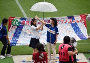 突然振り出した激しい雨の中、両チームのファンにピッチ上から笑顔であいさつする栗田るみ港北区長