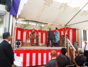 近隣の篠原八幡神社(篠原町)の宮司・水谷幸世(ゆきよ)さんを招き、新しく完成した舞殿で、厳(おごそ)かに式典(儀式)が行われた。司会は同実行委員会の岩田清さん(左)