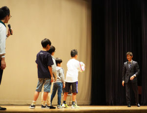 子どもたちにもステージ上でボールの取り方・投げ方を指南しました