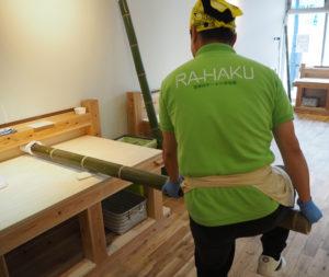 """篠原町で岩岡館長と一緒に伐採したという青竹に足をかけ、体重をかけながら麺生地を徐々に伸ばしていく。瀧上さん自身、栃木県佐野市に出向いて製法の""""修業""""を行った"""