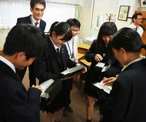 逆瀬川貴司副校長(左奥)、関口奈緒美顧問が見守る中、記念に贈呈された文鎮に喜ぶ書道部員たち。設置を担当する株式会社エフォートの鈴木剛(たけし)さん(右奥)も同席した