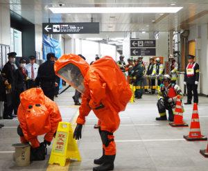 菊名駅で初めて警察・消防・東急電鉄・JR東日本の4者が合同でテロ対策訓練を行った。「不審な液体」への対処を行う特別高度救助部隊。右奥が設置された消防の指揮本部(2020年1月24日14時10分頃)(訓練)