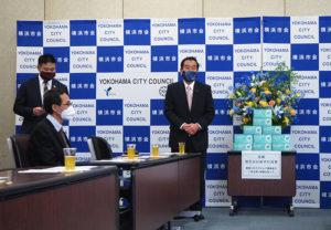 マスク寄贈式の冒頭で「日本アフリカ友好横浜市会議員連盟」の会長を務める佐藤さんがあいさつ。最左は都筑区選出の市会議員で同連盟事務局長の草間剛(つよし)さん