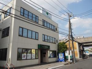 地下鉄ブルーライン新羽駅から徒歩約4分、宮内新横浜線(右手)に近い新羽町に、新たに新本社ビルを構えた株式会社宮崎通信。正面左側には台数を大幅に増強した駐車場への入口も(5月14日)