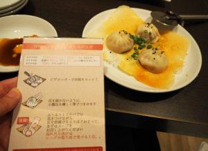 「羽根つき焼き小籠包」が出されるまでの間、にんにくを焦がしたという香港ラー油や、特製酢味噌などでタレを作り、待つ。到着したらピザカッターで「Y字」にカットして食す。食べ方の指南も