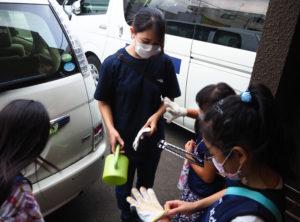 児童の有志が清掃活動を行う。同園の責任者でマネージャ―の中川朋香さん(中央)とともに出発準備