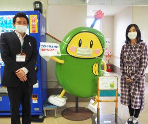 2011(平成23)年に誕生したキャラクター「まめっち」と、櫻井所長(左)、山口さん。スタッフが考案、後に着ぐるみも登場するなど地域で親しまれている