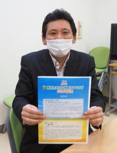 「横浜市大豆戸地域ケアプラザ20周年記念リーフレット」を手に。櫻井所長自らのあいさつも掲載している