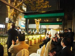 初めての点灯式にも参加していた伴久之社長、新横浜町内会の金子会長がスイッチを押し、灯りが点った瞬間には大きな拍手が。後方にはくらしの友が経営する「新横浜KTビル」も見える(12月8日18時頃)