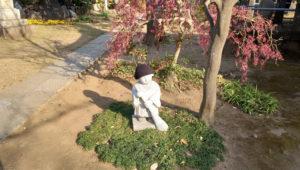 暖かそうな帽子をかぶって箒を持つ金蔵寺「小僧さんの像」(2020年12月、林宏美さん撮影)
