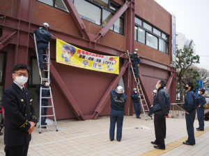 「コロナ禍に負けない」春の火災予防運動が港北区でスタート。港北火災予防協会の協力で製作した横断幕を区総合庁舎に初掲示。吉田署長(最左)も激励に訪れた(2月26日)
