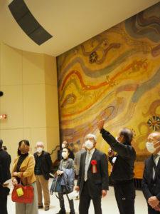 臼井館長(左から2人目)が港北区連合町内会の川島会長(同3番目)らに館内のリニューアルされたポイントを解説した