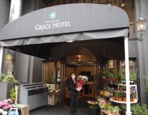 先月(2021年)4月17日にオープンした「新横浜グレイスホテルのお花屋さん」前で、広報担当の丸山さん。新横浜キュービックプラザ「ぐるめストリート」向い側のホテル出入口に、所狭しと花が並んでいる(5月13日)