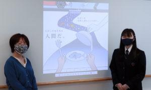 ポスターを制作した松岡さん(右)。副担任を務める折橋慧(けい)さんと