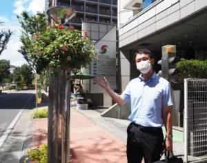 暑さ厳しい夏の日に。F・マリノス通りにあるシルバービル前にて。「美しい花たちに癒されています」と新横浜で勤務し16年目を迎えた司法書士の佐伯さん