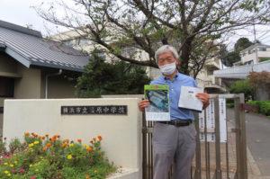 生徒たちに配られた記念のクリアファイルとお菓子を手にする川島会長
