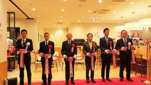 オープンに先立ち、テープカットが行われた。写真右から川本理事長、加藤本部長、川上社長、川口理事長、松永社長、真道支店長。右手がドトールコーヒー、左手が城南信金瀬谷支店側となる